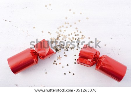 Festive surprise concept with opened red bon bon Christmas cracker and glitter stars on white wood table with copy space for your text here.  - stock photo