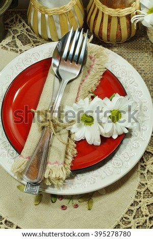 Festive table, plate, silverware and flowers - in folk style