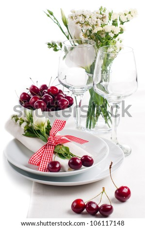 Festive table setting and decoration with fresh flowers and sweet cherry - stock photo
