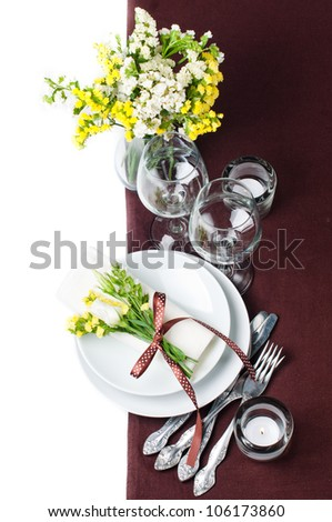 Festive table setting and decoration with fresh flowers in brown and yellow - stock photo
