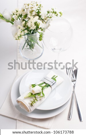 Festive table setting and decoration with fresh flowers in white colors - stock photo
