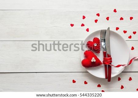 thiết lập cho Ngày Valentine với nĩa, dao và trái tim trên một chiếc bàn gỗ trắng bảng lễ hội.  Không gian cho văn bản.  Top xem.