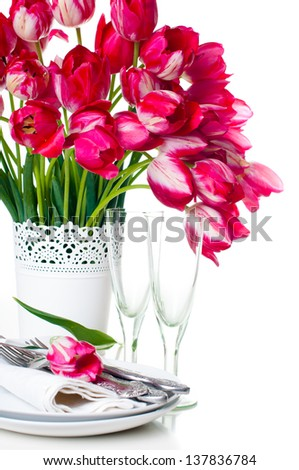 Festive table setting with a bouquet of bright pink tulips in a white vase and vintage wine glasses, isolated - stock photo