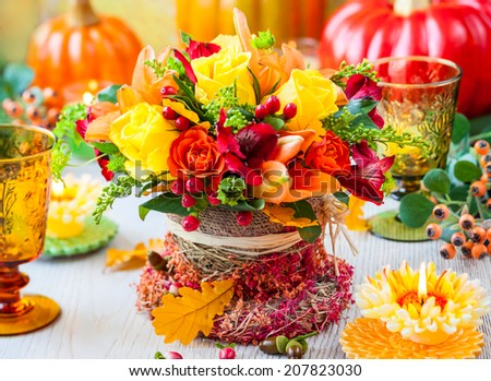 Festive table setting with basket of autumn flowers,candle and pumpkin. Selective focus. - stock photo