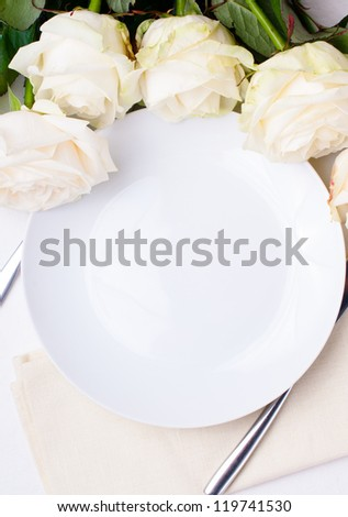Festive table setting with beige roses, wine glasses, candles, napkins and cutlery - stock photo