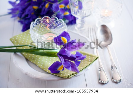 Festive table setting with purple iris flowers, vintage cutlery and candles. - stock photo