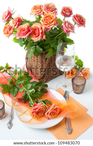 Festive table setting with roses and candles in shades of orange on a white background - stock photo