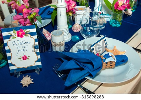 Festive table setting with starfishes, napkins, glasses and candles, bright summer table decor. - stock photo