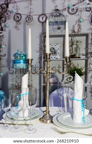 Festive table with candles in white - light blue style - stock photo