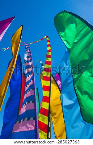 Festive, tall, colorful flags close together are flapping in breezy, windy conditions under a cloudless blue sky.