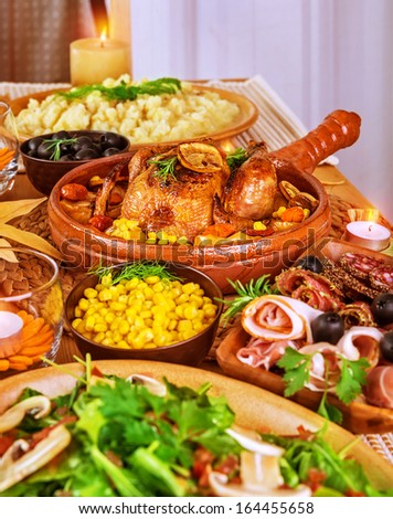 Festive Thanksgiving table, traditional autumn holiday, oven baked chicken, fresh salad, potato garnish, candle decoration, happy celebration concept  - stock photo