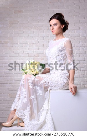 Festive wedding photo of chic sexy bride in white evening lace dress,posing in the studio. - stock photo