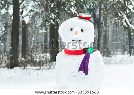 Festive winter three-ball dressed snowman with smiley face and carrot nose - stock photo