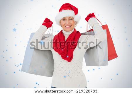 Festive woman smiling at camera holding shopping bags against snow falling