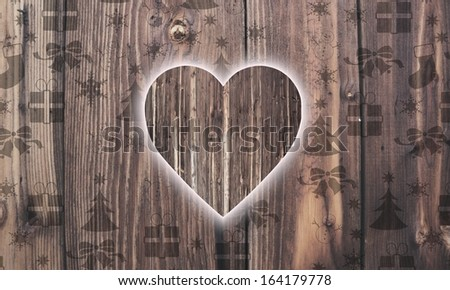 festive wooden heart label on wood with burned in christmas symbols such as snowflakes presents and stars