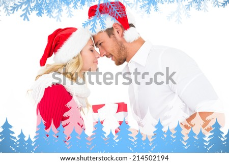 Festive young couple exchanging presents against frost and fir trees - stock photo