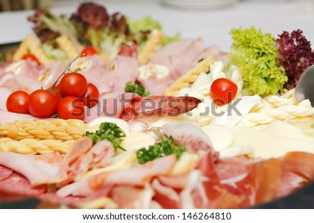 Festively arranged meat and chees products on the plate, focused to tomato - stock photo