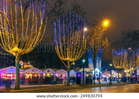 Festively decorated and illuminated Champs Elysees and Christmas market at night, France - stock photo