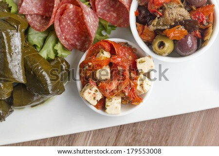 Feta cheese and sundried tomato on an antipasto platter. - stock photo