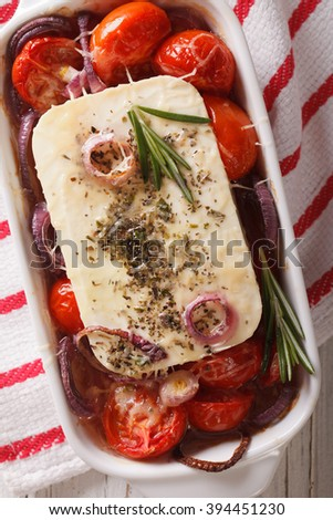 Feta cheese baked with tomatoes and onions in baking dish closeup. vertical view from above