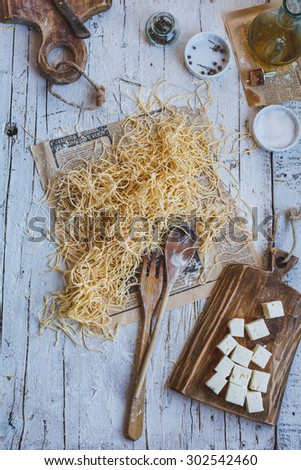 Feta cheese cubes on a cutting board with homemade tagliatelle pasta over on old newspaper from above on white retro wooden table with bottle of olive oil for preparing traditional dinner food.  - stock photo