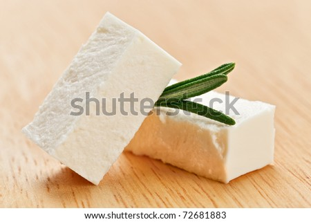 Feta cheese cubes with rosemary twig on wooden chopping board - stock photo