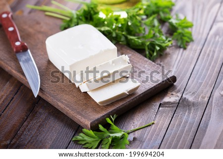 Feta cheese on board on wooden background. Selective focus, horizontal. - stock photo