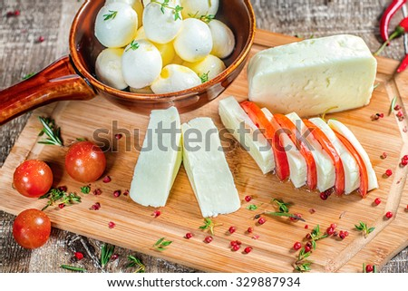 Feta cheese or mozzarella cheese is sliced on a wooden board with tomatoes and red pepper. Feta cheese or mozzarella cheese decorated with red pepper. - stock photo