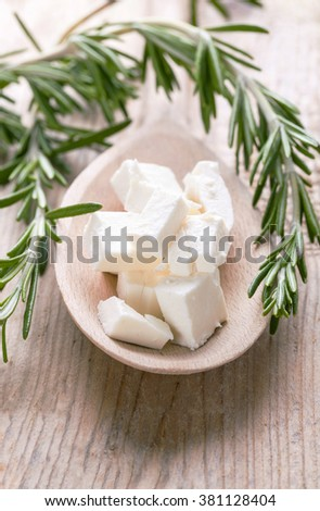 feta cheese portion on a wooden spoon with rosemary - stock photo