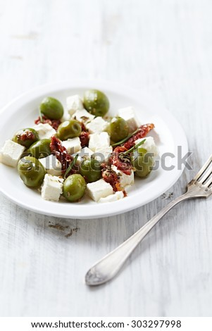Feta cheese with green olives and dried tomatoes - stock photo