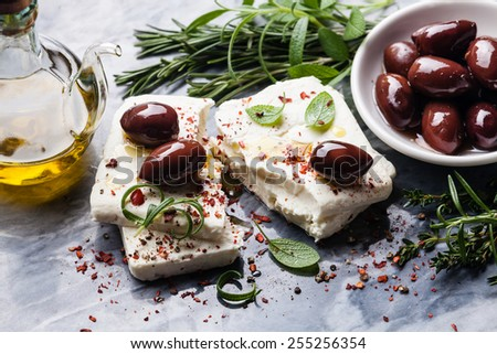 Feta cheese with olives and green herbs on gray marble background - stock photo