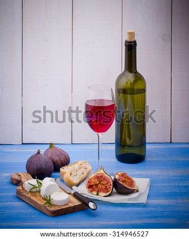 Feta cheese with ripe figs and wine on blue, vertical