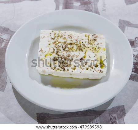feta traditional cheese with oregano in a dish on a table