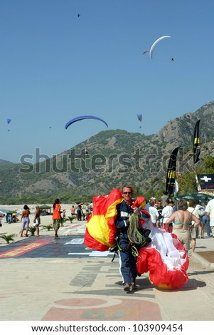 FETHIYE, TURKEY - OCTOBER 22: Paraglider landing to Fethiye beach, October 22, 2003 in Fethiye, Turkey. Every year many paragliders attend to Fethiye Air Festival.