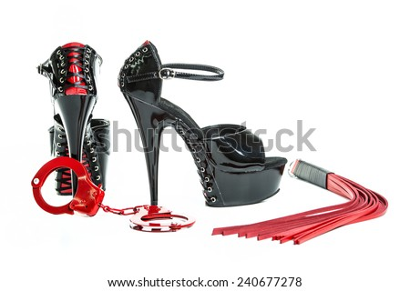Fetish and bondage stuff for role playing and BDSM: high heels shoes, leather whip and hand cuffs - stock photo