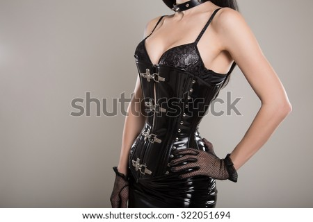 Fetish dominatrix girl in leather corset, mini skirt and gloves  - stock photo