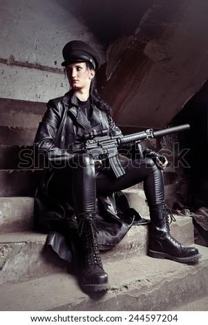 Fetish girl holding gun - stock photo