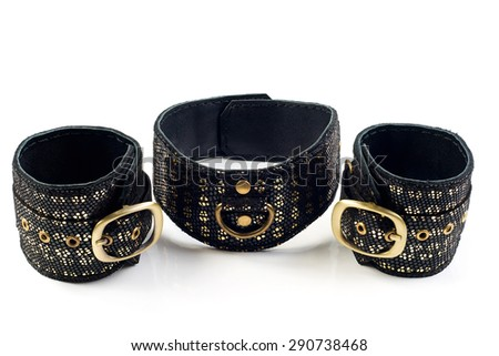 Fetish Hand cuffs and collar a made of black and gold leather - stock photo