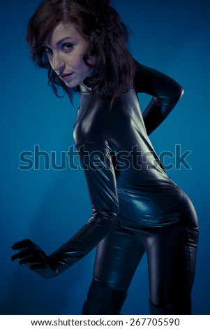 Fetish, sexy brunette in black latex bodysuit tight and wild poses - stock photo