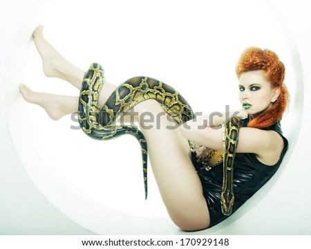 fetish woman with creative make up holding Python - stock photo