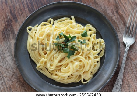 Fettuccine alfredo with butter, parmesan and parsley on a tin plate. - stock photo