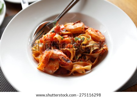Fettuccine in tomato sauce with shrimp and tomatoes - stock photo