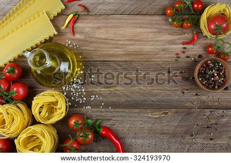 Fettuccine, lasagna, oil and fresh tomatoes on wooden background - stock photo