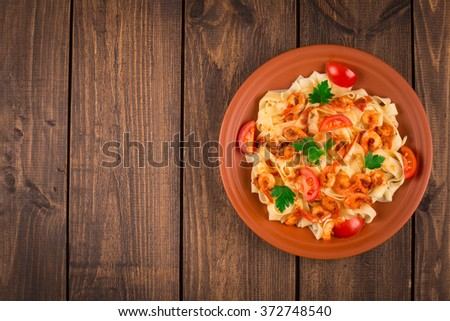 Fettuccine pasta with shrimp tomatoes and herbs. wooden background - stock photo