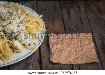 Fettuccine with chicken and cream sauce on a wooden vintage background