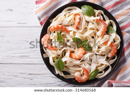 fettuccini pasta in cream sauce with shrimp on a plate on the table. horizontal view from above