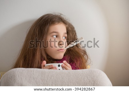 Fever, cold and flu concepts. Little girl holding thermometer in her mouth, looking away and holding a cup of tea at home.