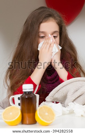 Fever, cold and flu concepts. Little girl sneezing in to tissue. Lady blowing her nose while sitting on her bed at home. - stock photo