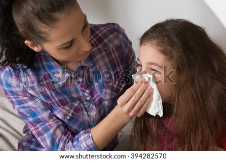 Fever, cold and flu concepts. Sick child wiping or cleaning nose with tissue while her mother helping her. - stock photo