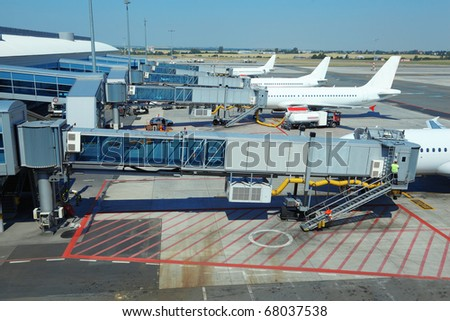 few airliners parked at airport. boarding passengers. service technician - stock photo